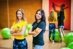 Twee jonge atletische lichaamsbouwvrouwen in gymnastiek Stock Foto's