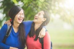 Twee jonge Aziatische studentenlach, die samen gekscheren rond stock foto's