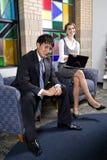 Twee jonge bedrijfsarbeiders in bureauwachtkamer royalty-vrije stock afbeeldingen