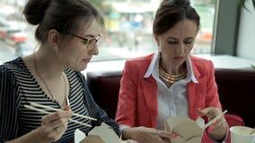 Twee jonge bedrijfsmeisjes bij lunch zitten en eten heerlijke noedels in dozen en drinken koffie Lunch op het werk stock footage