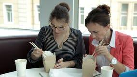 Twee jonge bedrijfsmeisjes bij lunch zitten en eten heerlijke noedels in dozen en drinken koffie Lunch op het werk stock video