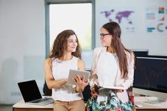 Twee jonge bedrijfsmeisjes die elkaar bekijken stock afbeeldingen