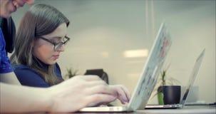 Twee Jonge bedrijfsmensen die computer in het bureau met behulp van Twee collega's die van de decorateur aan innovatief samenwerk stock videobeelden