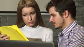 Twee jonge bedrijfsmensen die documenten bespreken op het kantoor stock footage