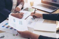 Twee jonge bedrijfsmensen die op bedrijfsdocument richten stock foto