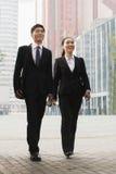 Twee jonge bedrijfsmensen die, Peking, China in openlucht lopen Royalty-vrije Stock Afbeeldingen