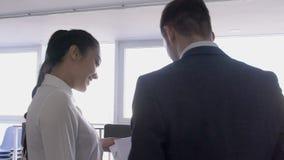 Twee jonge beroeps bespreken ideeën voor bedrijfsbevordering in grote bedrijf, mens en vrouw die, het spreken de bevinden zich stock videobeelden