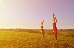 Twee jonge blonde meisjes in sporten past praktijkyoga op een schilderachtige groene heuvel aan stock afbeeldingen