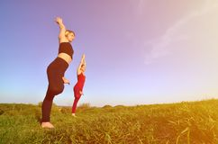 Twee jonge blonde meisjes in sporten past praktijkyoga op een schilderachtige groene heuvel aan royalty-vrije stock fotografie