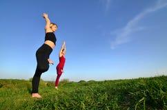 Twee jonge blonde meisjes in sporten past praktijkyoga op een schilderachtige groene heuvel aan stock foto's