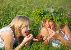 Twee jonge blonde vrouwen die aardbeien eten Royalty-vrije Stock Foto