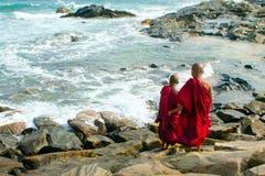 Twee jonge Boeddhistische monniken in rode robes bevinden zich bij de kust stock fotografie