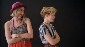 Twee jonge charmante vrouwelijke vrienden hebben conflict, beledigde vrouwen die zich met gekruiste die handen bevinden op zwarte stock video