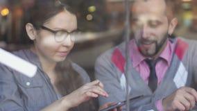 Twee jonge, creatieve en bedrijfsmensen in een koffie stock footage