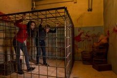 Twee jonge die Halloween-slachtoffers in een metaalkooi worden gevangengenomen die proberen aan stock fotografie