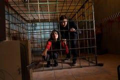 Twee jonge die Halloween-slachtoffers in een metaalkooi worden gevangengenomen, meisje pul stock foto's