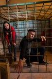 Twee jonge die slachtoffers in een metaalkooi worden gevangengenomen, jongen die zijn Ha trekken royalty-vrije stock afbeelding