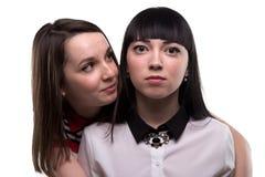 Twee jonge donkerbruine ernstig en vrouwen die - glimlachen royalty-vrije stock foto