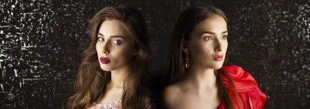 Twee Jonge donkerbruine vrouwen op de donkere achtergrond van de studiomuur Royalty-vrije Stock Foto
