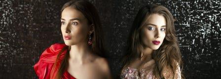 Twee Jonge donkerbruine vrouwen op de donkere achtergrond van de studiomuur Stock Afbeelding