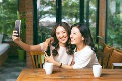 Twee jonge en aantrekkelijke wijfjes die selfie terwijl het zitten in de koffie nemen royalty-vrije stock foto's