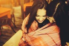 Twee jonge en mooie meisjes die pret in koffie hebben Stock Foto's