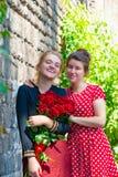 Twee jonge en mooie meisjes, met een boeket van rode rozen bevinden zich op de achtergrond van een oude bakstenen muur royalty-vrije stock fotografie