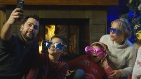 Twee jonge families die voor een Kerstmisfoto stellen stock videobeelden