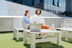 Twee jonge freelancers die in de koffie buiten werken royalty-vrije stock foto's