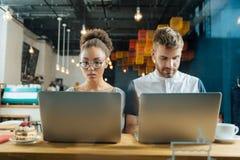 Twee jonge freelancers die hard terwijl het zitten in koffie werken royalty-vrije stock afbeeldingen