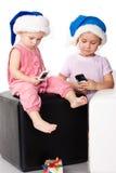 Twee jonge geitjes in de hoeden van de Kerstman met mobiles stock foto's