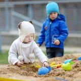 Twee jonge geitjes die in een zandbak spelen Royalty-vrije Stock Foto's
