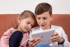 Twee jonge geitjes die met digitale tablet spelen Stock Afbeeldingen