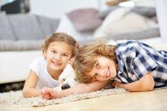 Twee jonge geitjes die met hond thuis spelen Stock Afbeeldingen
