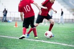 Twee jonge geitjes die voetbal spelen stock foto's