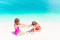 Twee jonge geitjes die zandkasteel maken en pret hebben bij tropisch strand stock fotografie