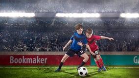 Twee jonge geitjes fotball spelers die voor de bal worstelen royalty-vrije stock afbeeldingen