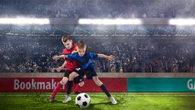 Twee jonge geitjes fotball spelers die voor de bal worstelen stock foto
