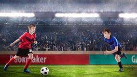 Twee jonge geitjes fotball spelers die voor de bal worstelen royalty-vrije stock foto's