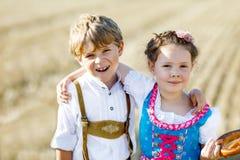 Twee jonge geitjes, jongen en meisje in traditionele Beierse kostuums op tarwegebied stock foto