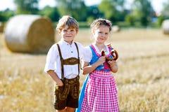 Twee jonge geitjes, jongen en meisje in traditionele Beierse kostuums op tarwegebied Stock Afbeeldingen