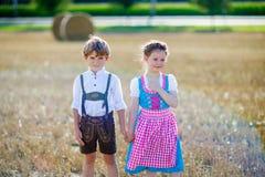 Twee jonge geitjes, jongen en meisje in traditionele Beierse kostuums op tarwegebied Royalty-vrije Stock Fotografie