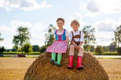 Twee jonge geitjes, jongen en meisje in traditionele Beierse kostuums op tarwegebied Stock Afbeelding