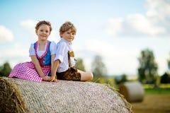 Twee jonge geitjes, jongen en meisje in traditionele Beierse kostuums op tarwegebied met hooibalen stock afbeelding