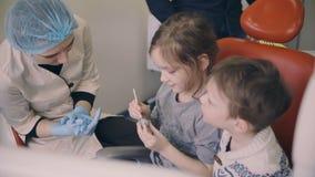 Twee jonge geitjes, jongens en meisjeszitting als tandartsvoorzitter vóór de tandcontrole Broer en zustervorm met jonge arts stock video