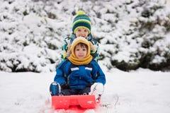 Twee jonge geitjes, jongensbroers, die met loodje in de sneeuw glijden, wintertijd stock foto's