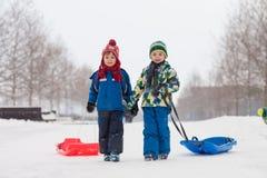 Twee jonge geitjes, jongensbroers, die met loodje in de sneeuw glijden, wintertijd stock afbeelding
