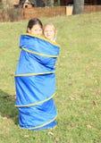 Twee jonge geitjes - meisjes in blauwe jonge geitjestunnel Stock Afbeeldingen