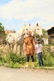 Twee jonge geitjes - meisjes die op twee paarden letten Stock Afbeeldingen