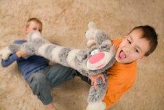 Twee jonge geitjes met een stuk speelgoed op de vloer Stock Fotografie